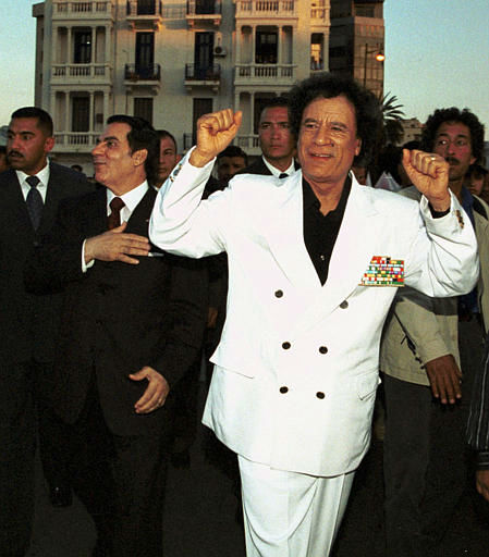 Libyan leader Moammar Gadhafi, right, and Tunisian President Zine el Abidine Ben Ali, left, gesture towards residents as they walk through downtown Tunis, Tuesday, May 20, 2003.  <span class=meta>(AP Photo&#47; Hassene Dridi)</span>
