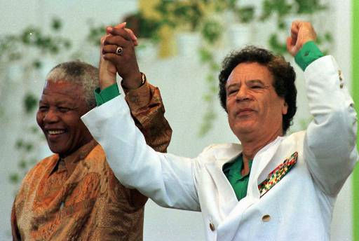 "<div class=""meta image-caption""><div class=""origin-logo origin-image ""><span></span></div><span class=""caption-text"">Libyan President Moammar Gadhafi, right, and South African President Nelson Mandela salute the crowd as they arrive at the congress center in Zuwarah, 60 miles west of Tripoli, Wednesday, Oct. 29, 1997.  (AP Photo/ Enric Marti)</span></div>"