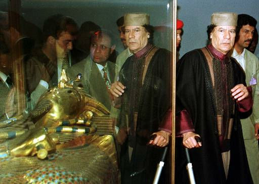 The image of Libyan President Moammar Gadhafi is reflected in the glass as he visits the room displaying the Tutankhamen grave treasures at the Egyptian museum in Cairo Sunday, Feb. 7, 1999.  <span class=meta>(AP Photo&#47; Enric Marti)</span>