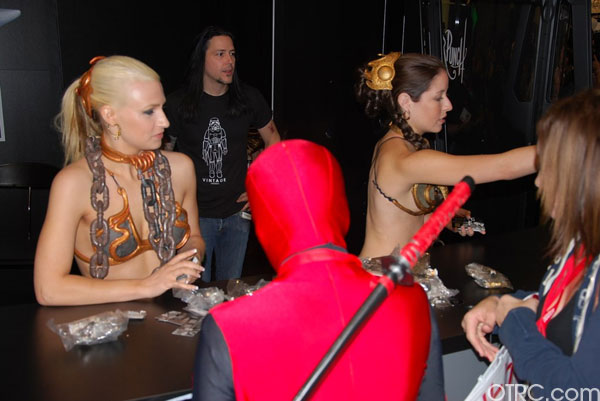 Exhibit workers dressed as Princess Leia give  merchandise to a fan dressed as Deadpool at Comic-Con 2010 in San Diego