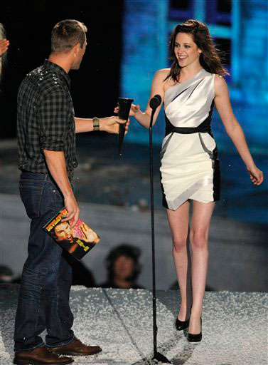Aaron Eckhart, left, presents Kristen Stewart...