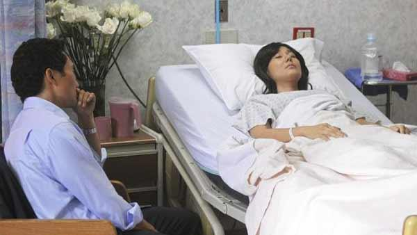 Jin-Soo Kwon (Daniel Dae Kim) sits and watches his wife Sun-Hwa Kwon (Yunjin Kim) as she sleeps on a hospital bed.