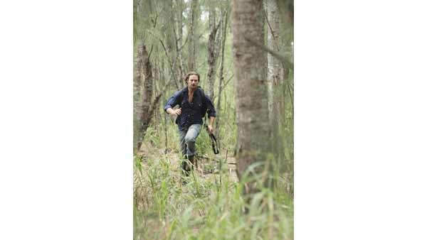 Sawyer (Josh Holloway) runs through a forest.