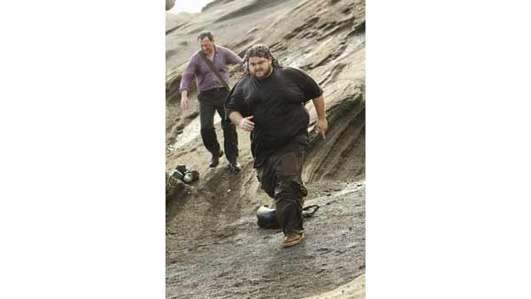Ben Linus (Michael Emerson) and Hurley (Jorge Garcia) run down the rocks. They will later become guardians of the Island, and the best of friends.