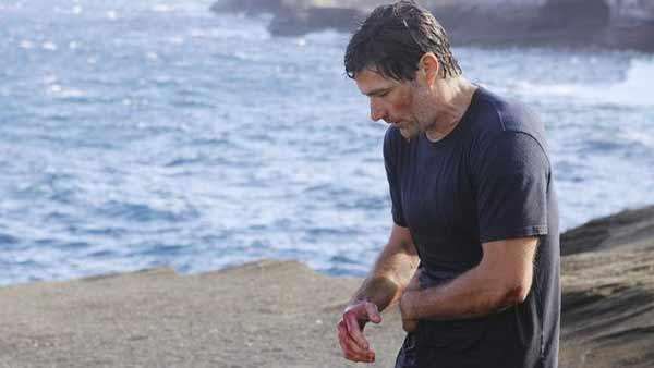 Jack Shepard (Matthew Fox) clutches his side. Earlier, he was stabbed by the Man in Black, who he then pushed over a cliff.