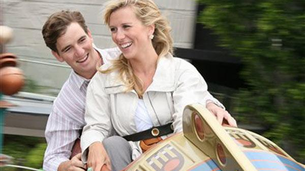 In this photo released by Disneyland, New York Giants' Eli  Manning, left, and his new wife Abby McGrew take a ride on the Astro Orbitor at Disneyland in Anaheim, Calif., on Wednesday, May 7, 2008.