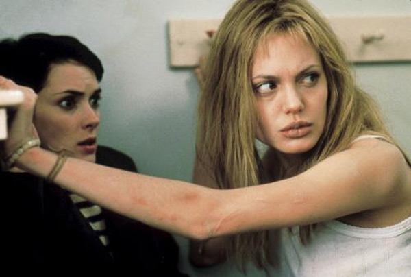 "<div class=""meta ""><span class=""caption-text "">In the early 1990's, Angelina began to suffer from depression and began cutting herself.  She told Allure in 2004, 'I had that problem early on when I couldn't feel a bond with another human being.' Pictured: Winona Ryder and Angelina Jolie in a scene from the 1999 film 'Girl, Interrupted', which depicted the lives of female mental patients.  (Photo courtesy of Sony Pictures)</span></div>"