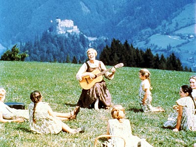 Pictured from Julie Andrews as Maria, singing and playing guitar for the children in a scene from 'The Sound of Music'.