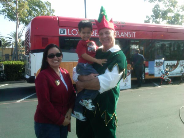 A family poses with Garth the Elf  after donating toys at the Stuff-A-Bus event at Los Cerritos Center on Thursday, Nov. 18, 2010. <span class=meta>(KABC)</span>
