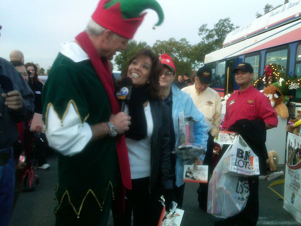A local woman joins Garth the Elf at a Stuff-A-Bus event at Ontario Mills on Friday, Dec. 3, 2010. <span class=meta>(KABC)</span>