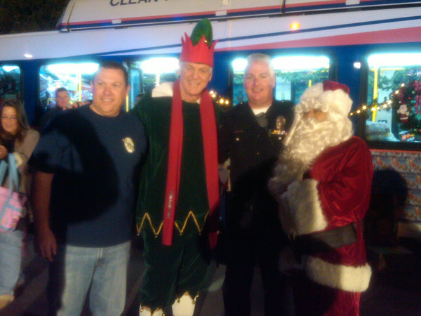 Garth the Elf poses with Santa and members of the Ontario Police Officers Association at Stuff-A-Bus at Ontario Mills on Friday, Dec. 3, 2010. <span class=meta>(KABC)</span>