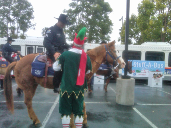 Garth the Elf chats with a member of the Santa Ana Police Department at the Stuff-A-Bus event at the Honda Center in Anaheim on Friday, Dec. 17, 2010. <span class=meta>(KABC)</span>