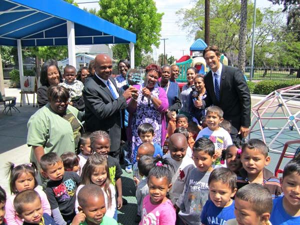 Drew Childhood Development Corporation: Officials and kids at the Drew Childhood Development Corporation take a group photo with ABC7&#39;s Elex Michael, holding the &#36;7,000 &#39;Pay It Forward token.&#39; Read more about the Drew Childhood Development Corporation. <span class=meta>(KABC Photo)</span>