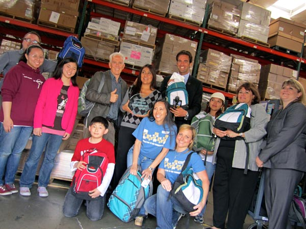 Volunteers and Giving Children Hope executives pose with backpacks headed for homeless children.