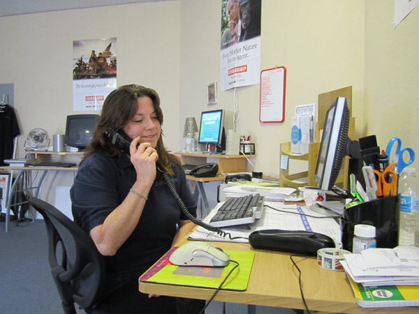 Kathy Serianni, founder of the Smiles for Seniors Foundation, answers phone calls from seniors in need at the organization's headquarters in Yucaipa, Calif.