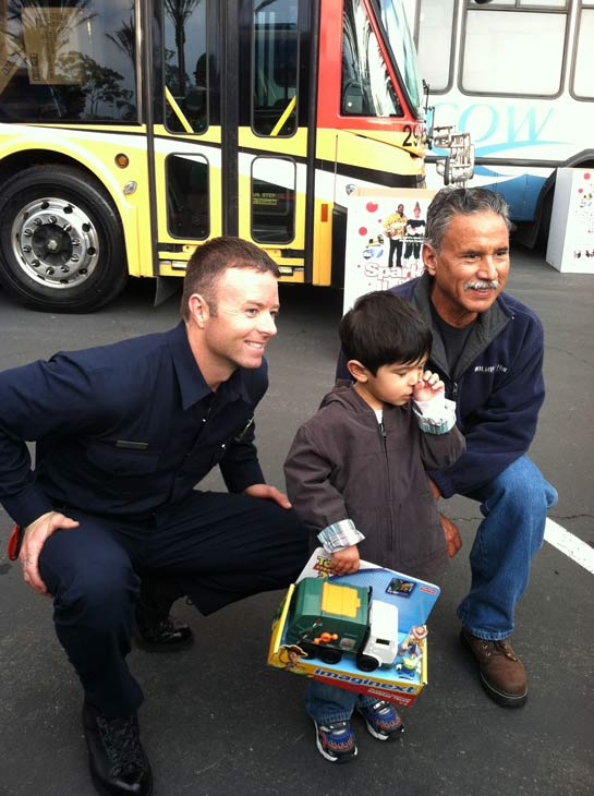 L.A. County firefighters pose with a boy at the &#39;Spark of Love Toy Drive&#39; at Los Cerritos Center on Friday, Nov. 18, 2011. <span class=meta>(KABC Photo)</span>