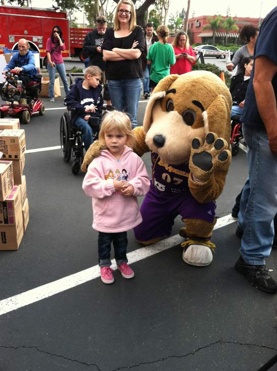 "<div class=""meta ""><span class=""caption-text "">Sparky, the mascot for the Los Angeles Sparks, poses with a girl at the 'Spark of Love Toy Drive' at Los Cerritos Center on Friday, Nov. 18, 2011. (KABC Photo)</span></div>"