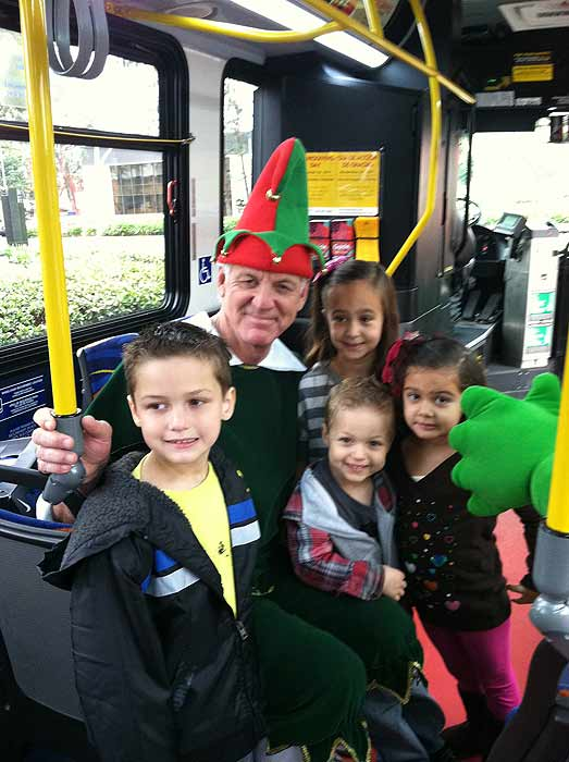 A family from Artesia joins Garth the Elf to &#39;Stuff-A-Bus&#39; full of toys at Los Cerritos Center on Nov. 18, 2011. <span class=meta>(KABC Photo)</span>