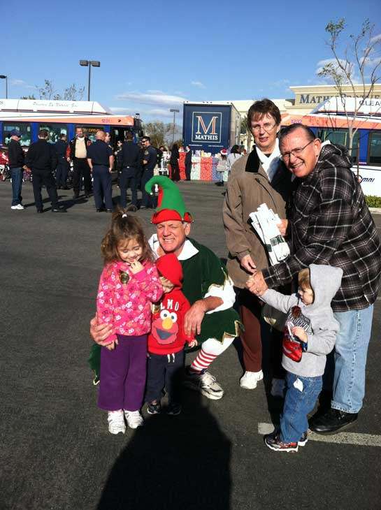 Garth the Elf poses with a family at the &#39;Spark of Love Toy Drive&#39; at Mathis Brothers in Ontario on Friday, Dec. 2, 2011. <span class=meta>(KABC Photo)</span>