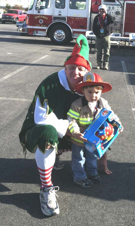 Garth the Elf poses with young firefighter at the &#39;Spark of Love Toy Drive&#39; at Mathis Brothers in Ontario on Friday, Dec. 2, 2011. <span class=meta>(KABC Photo)</span>