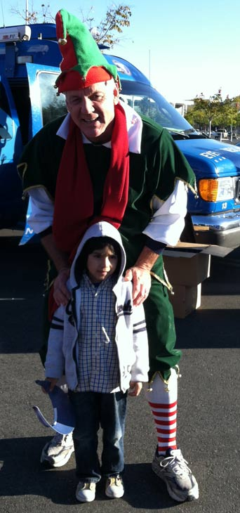 "<div class=""meta ""><span class=""caption-text "">Garth the Elf poses with a young boy at the 'Spark of Love Toy Drive' at Westfield Topanga Mall in Canoga Park on Friday, Dec. 9, 2011. (KABC Photo)</span></div>"