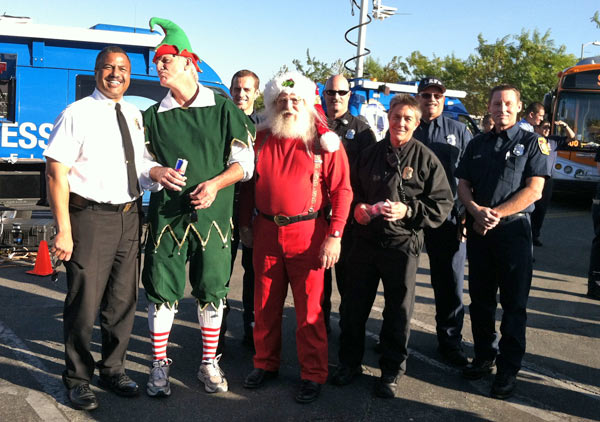 "<div class=""meta ""><span class=""caption-text "">Garth the Elf poses with Santa and members of the L.A. City Fire Department, including Chief Brian Cummings, at the 'Spark of Love Toy Drive' Stuff-A-Bus event at Westfield Topanga Mall in Canoga Park on Friday, Dec. 9, 2011. (KABC Photo)</span></div>"