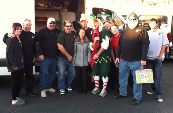 Garth the Elf poses with a group at the Stuff-A-Bus event at the Honda Center in Anaheim on Friday, Dec. 16, 2011. <span class=meta>(KABC Photo)</span>