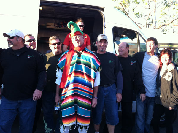 Garth the Elf puts on a poncho at the Stuff-A-Bus event at the Honda Center in Anaheim on Friday, Dec. 16, 2011.