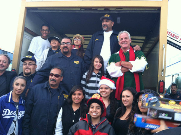 Garth the Elf poses with members of the Traffic Car Club at the Stuff-A-Bus toy drive at Mathis Brothers Furniture in Ontario on Friday, Nov. 30, 2012. <span class=meta>(KABC)</span>