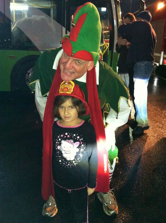 Garth the Elf poses with a future firefighter at the Stuff-A-Bus toy drive at Mathis Brothers Furniture in Ontario on Friday, Nov. 30, 2012.