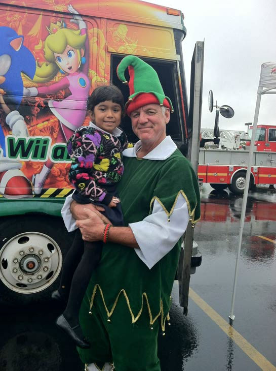 Garth the Elf poses with a young ABC7 viewer at the Stuff-A-Bus toy drive at Mathis Brothers Furniture in Ontario on Friday, Nov. 30, 2012.