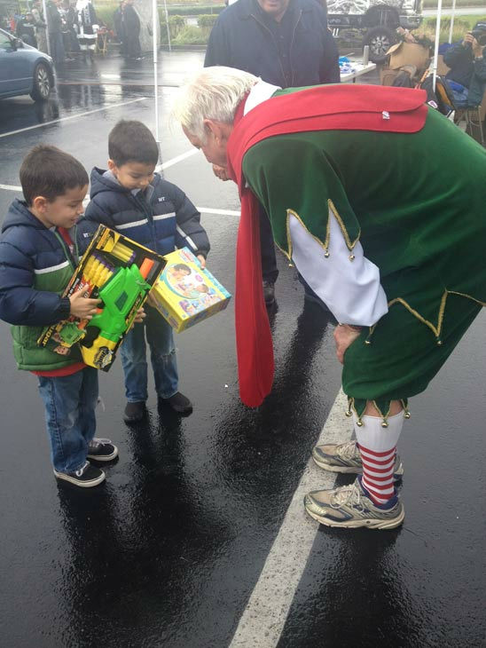 Garth the Elf talks with two young viewers at the Stuff-A-Bus event at Mathis Brothers Furniture in Ontario on Friday, Nov. 30, 2012.