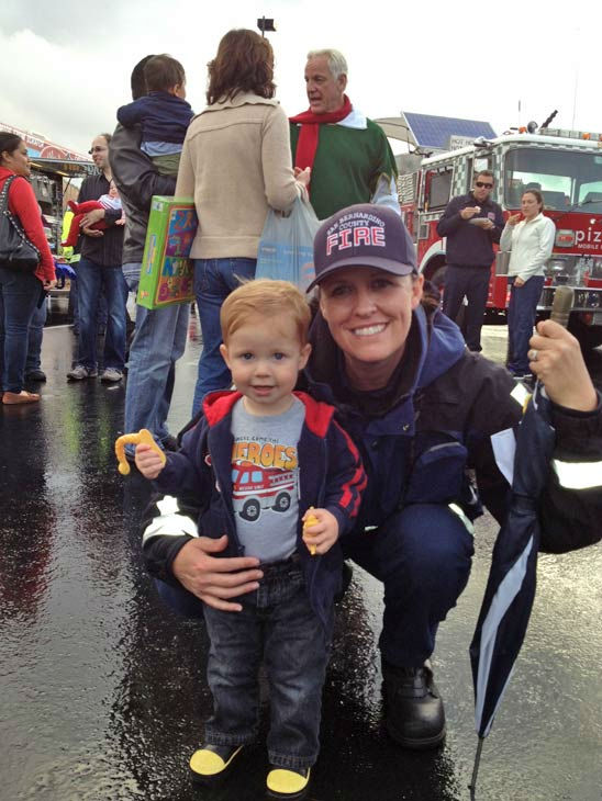 San Bernardino City Fire Engineer Kelly Hoverman and her son at the Stuff-A-Bus toy drive at Mathis Brothers Furniture in Ontario on Friday, Nov. 30, 2012. <span class=meta>(KABC)</span>