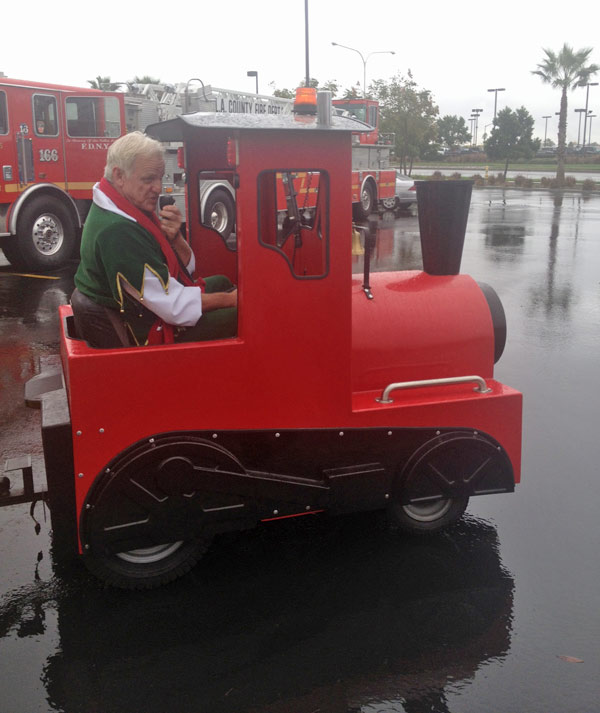 Garth the Elf drives the train at the Stuff-A-Bus event at Mathis Brothers Furniture in Ontario on Friday, Nov. 30, 2012. <span class=meta>(KABC)</span>