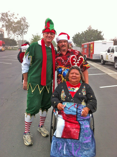 Garth the Elf and Shawn and Tara of Long Beach pose for a picture at the Stuff-A-Bus toy drive at Los Cerritos Center in Cerritos on Friday, Dec. 7, 2012. <span class=meta>(KABC Photo)</span>
