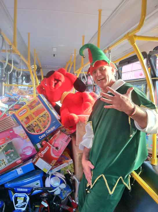 Garth the Elf poses inside a very stuffed bus No. 5 during the Stuff-A-Bus toy drive at Los Cerritos Center in Cerritos on Friday, Dec. 7, 2012. <span class=meta>(KABC Photo)</span>