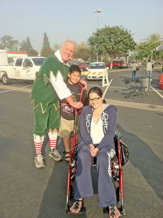 Downey residents pose for a picture with Garth the Elf at the Stuff-A-Bus toy drive at Los Cerritos Center in Cerritos on Friday, Dec. 7, 2012. <span class=meta>(KABC Photo)</span>