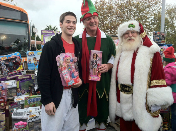 A generous donor, Garth the Elf, and Santa pose for a picture at the Stuff-A-Bus toy drive at the Westfield Topanga mall at Canoga Park on Friday, Dec. 14, 2012. <span class=meta>(KABC Photo)</span>
