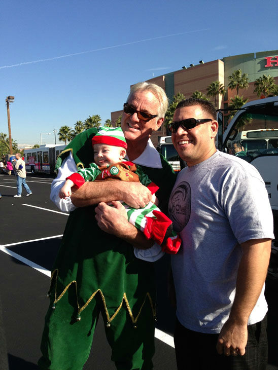 An ABC7 Viewer, baby Ruby, and Garth the Elf pose for a picture at the Stuff-A-Bus toy drive at the Honda Center in Anaheim on Friday, Dec. 21, 2012. <span class=meta>(KABC Photo)</span>