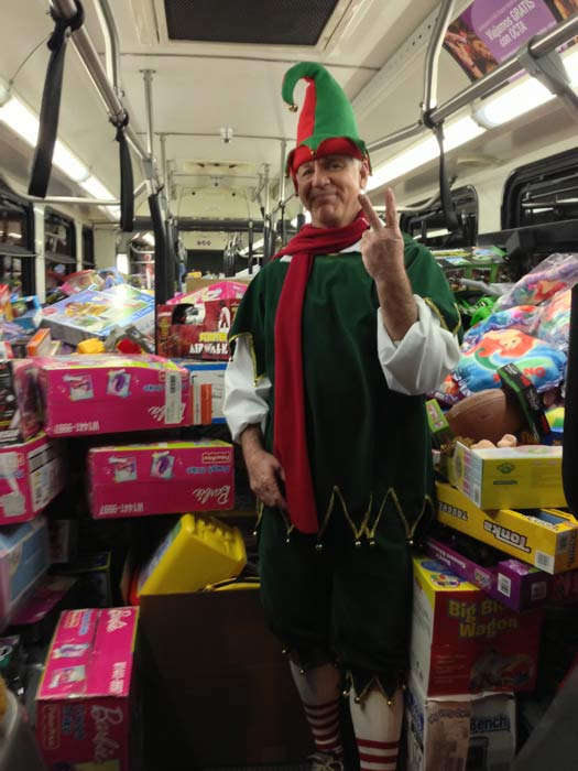 Garth the Elf poses inside a full bus at the Stuff-A-Bus toy drive at the Honda Center in Anaheim on Friday, Dec. 21, 2012. <span class=meta>(KABC Photo)</span>