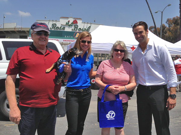 ABC7 Meteorologist Bri Winkler and Reporter Elex Michaelson pose with two donors and their dog at a fundraising event at the Rose Bowl in Pasadena to help the victims of the Oklahoma tornado on Wednesday, May 22, 2013. <span class=meta>(KABC)</span>