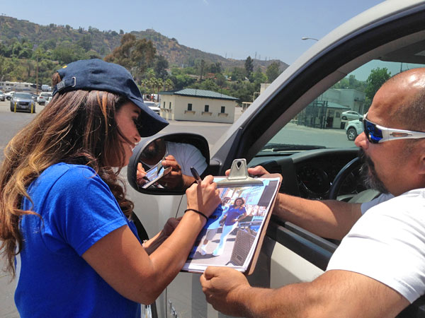 ABC7 Morning Traffic Reporter Alysha Del Valle signs a photo for ABC7 viewer Jim at a fundraising event at the Rose Bowl in Pasadena to help the victims of the Oklahoma tornado on Wednesday, May 22, 2013. <span class=meta>(KABC)</span>