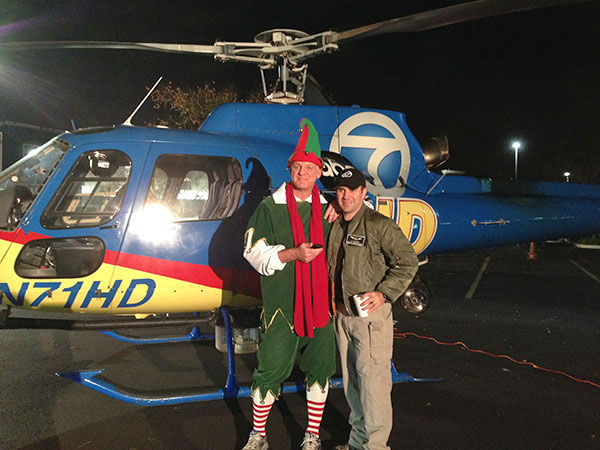 Garth the Elf poses with ABC7 helicopter reporter JT Alpaugh at the Stuff-A-Bus event at Mathis Brothers in Ontario on Friday, Dec. 6, 2013. <span class=meta>(KABC Photo)</span>