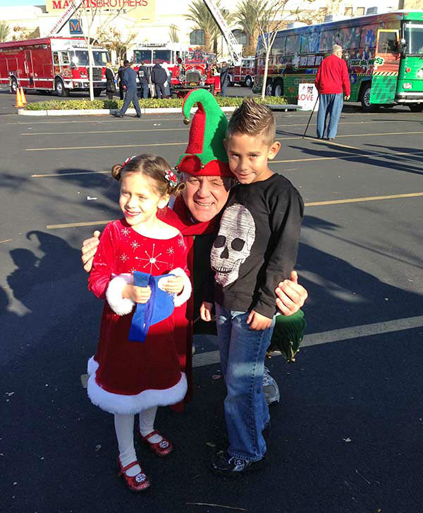 Garth the Elf poses with Joe and Ava from Eastvale at our Stuff-A-Bus event at Mathis Brothers in Ontario on Friday, Dec. 6, 2013. <span class=meta>(KABC Photo)</span>