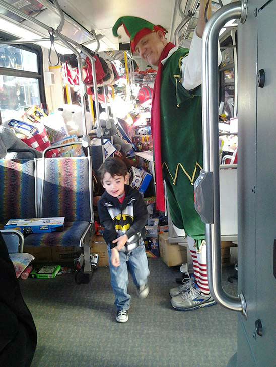 Anthony from Simi Valley helps Garth the Elf stuff a bus at our Spark of Love toy drive event at Westfield Topanga mall in Canoga Park on Friday, Dec. 13, 2013. <span class=meta>(KABC Photo)</span>
