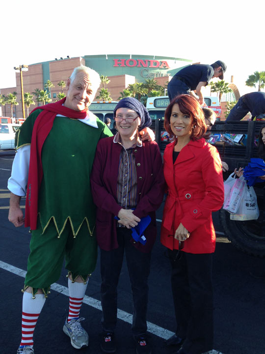 "<div class=""meta ""><span class=""caption-text "">Garth the Elf stands with an ABC7 viewer and ABC7 Orange County Bureau Chief Eileen Frere at the Stuff-a-Bus event at the Honda Center in Anaheim on Friday, Dec. 20. 2013. (KABC Photo)</span></div>"