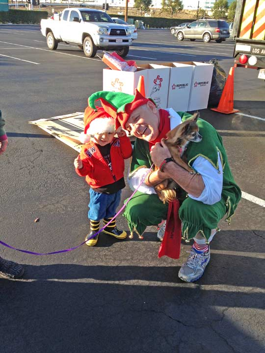 Garth the Elf poses with 2-year-old Lincoln and his dog CheeChee at the Stuff-a-Bus event at the Honda Center in Anaheim on Friday, Dec. 20. 2013. <span class=meta>(KABC Photo)</span>