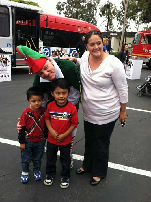 "<div class=""meta ""><span class=""caption-text "">Garth the Elf poses with a family at the 'Spark of Love Toy Drive' at Los Cerritos Center on Friday, Nov. 18, 2011. (KABC Photo)</span></div>"