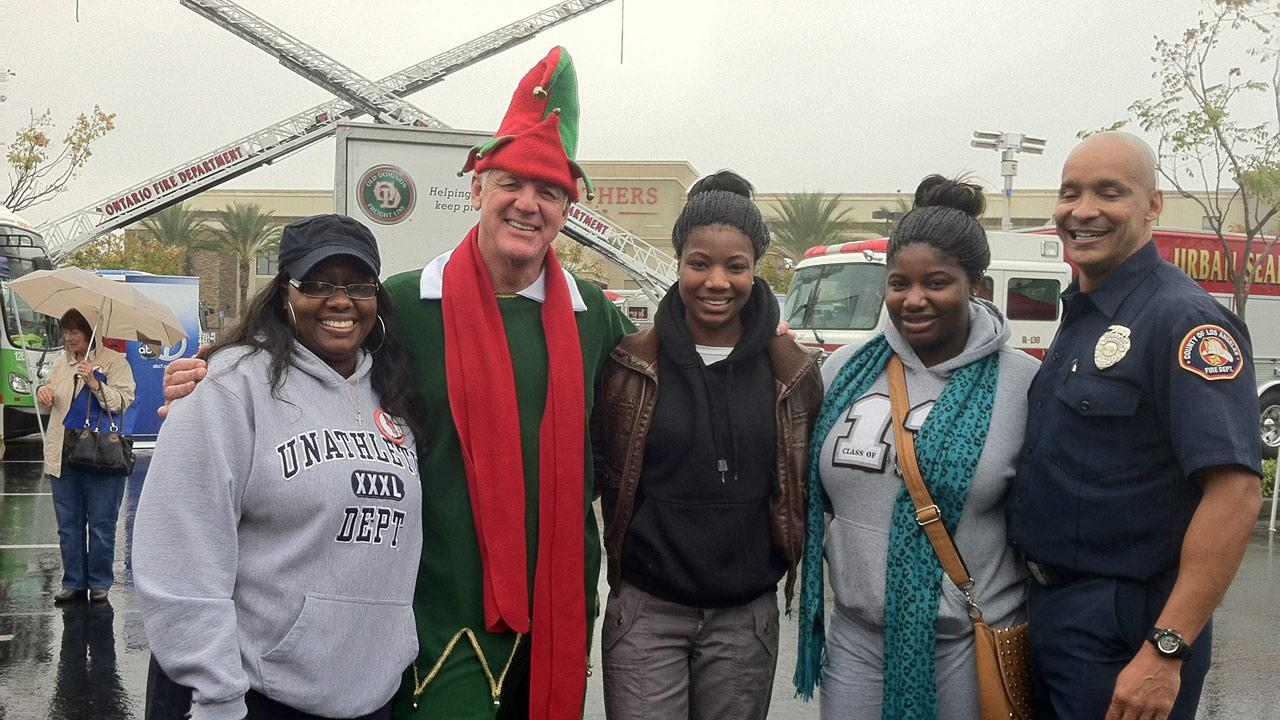 Garth the Elf poses for a picture with viewers at ABC7s Stuff-A-Bus event at Mathis Brothers Furniture in Ontario on Friday, Nov. 30, 2012.
