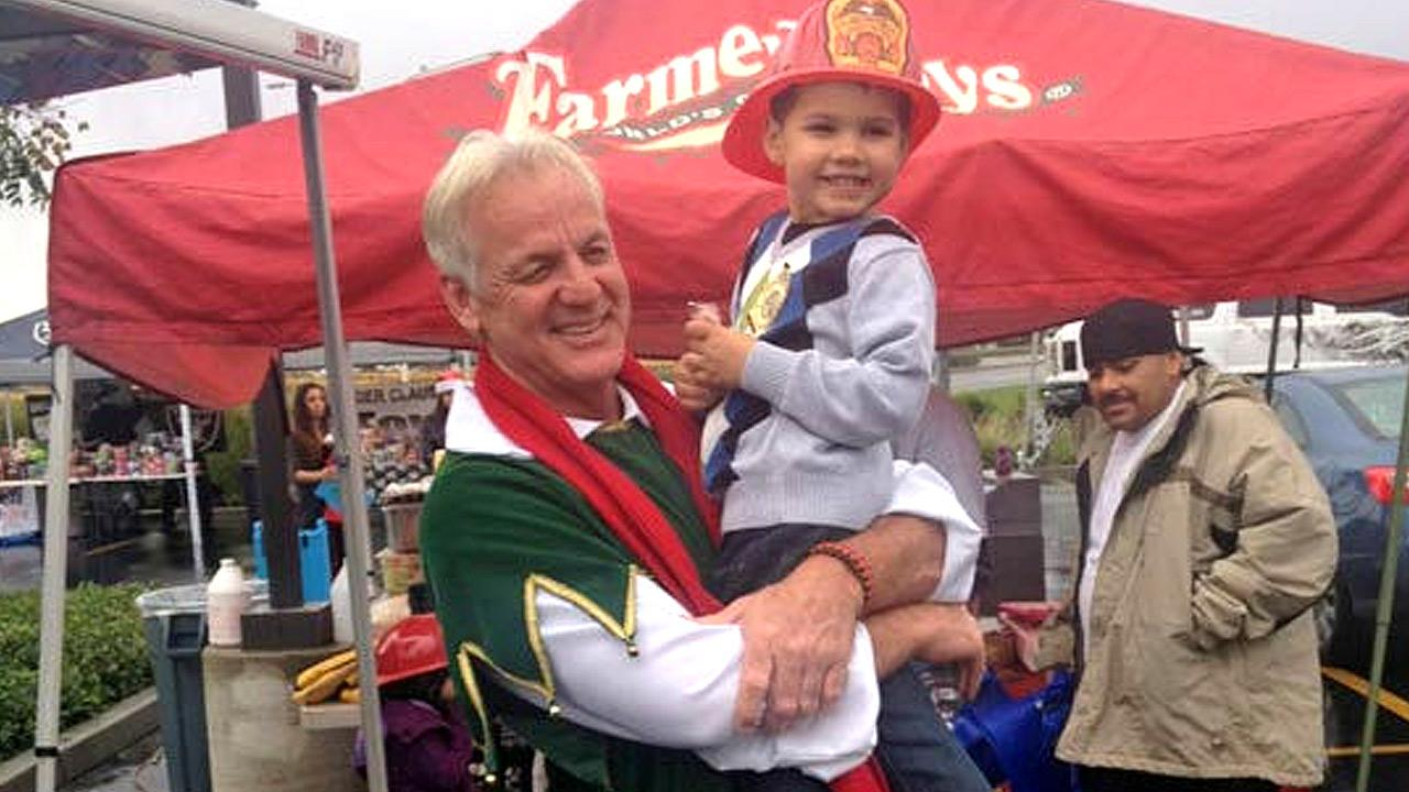 Garth the Elf poses with a future firefighter at the Stuff-A-Bus event at Mathis Brothers Furniture in Ontario on Friday, Nov. 30, 2012.